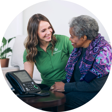Captioncall female employee assists female elder using CaptionCall table phone